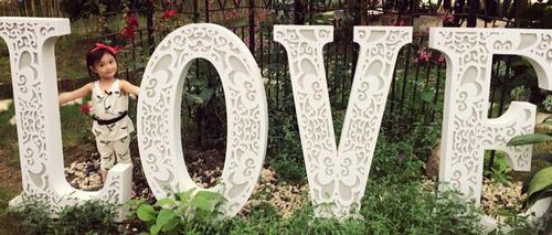 """照片中,奥莉头上戴着发箍,站在""""love""""雕塑旁,看起来十分可爱."""