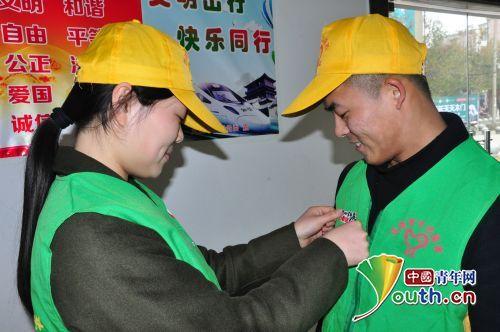 青年志愿者互相戴好服务春运标识.-幸福暖冬 志愿有我 九江桥工段青