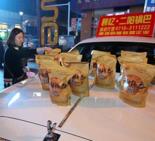 开劳斯莱斯卖锅巴 亲友豪车赞助路边叫卖襄阳特产锅巴
